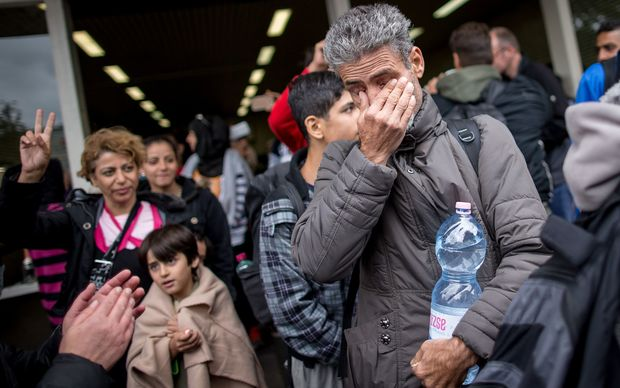 A refugee cries as he arrives at the main station in Dortmund, western Germany.