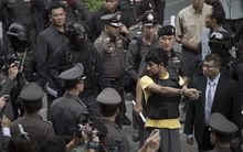 Erawan shrine bombing suspect Yusufu Mieraili during a reenactment, surrounded by police.
