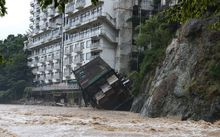 A hotel building falls into the floodwaters at Nikko mountain resort in Tochigi prefecture.
