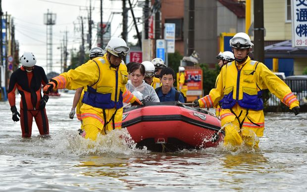 Rescue workers transport evacuees in a rubber boat through floodwaters.