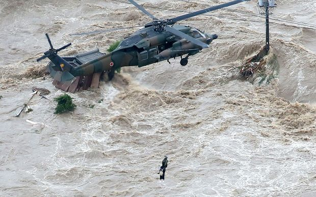 A local resident is rescued by a helicopter of the Gound Self Defense Force in a flooded area in Joso.