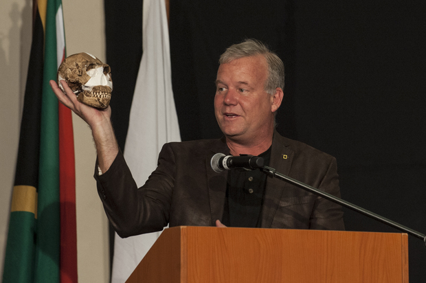 Professor Lee Berger holding up a Homo naledi skull at a press conference in Maropeng, South Africa.