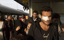 Refugees walk on a Berlin railway platform platform after getting out of a special train coming from Munich.