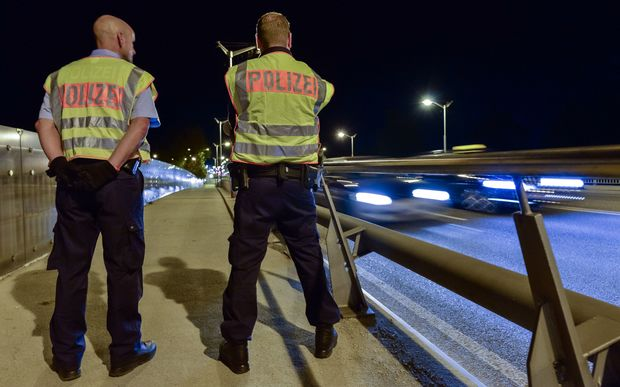 Two police officers observe the traffic at the border between Germany and Austria.