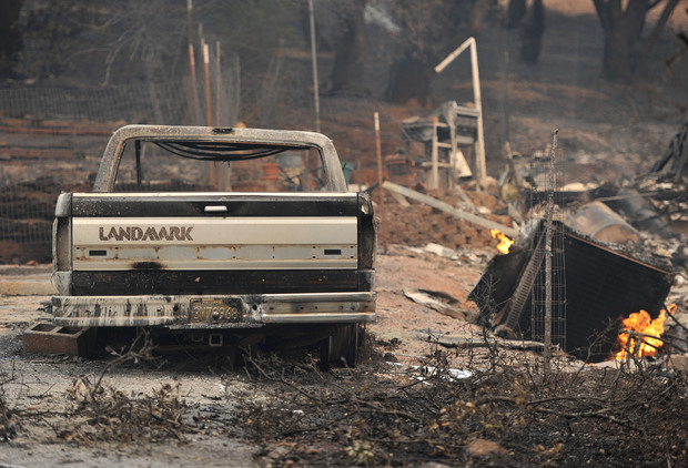 Flames from an open gas line burn next to a destroyed truck in the driveway of a home charred by the Valley fire in Middletown, California