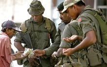 Soldiers buy a snack from a roadside trader as the army patrols the street after the 2008 coup.