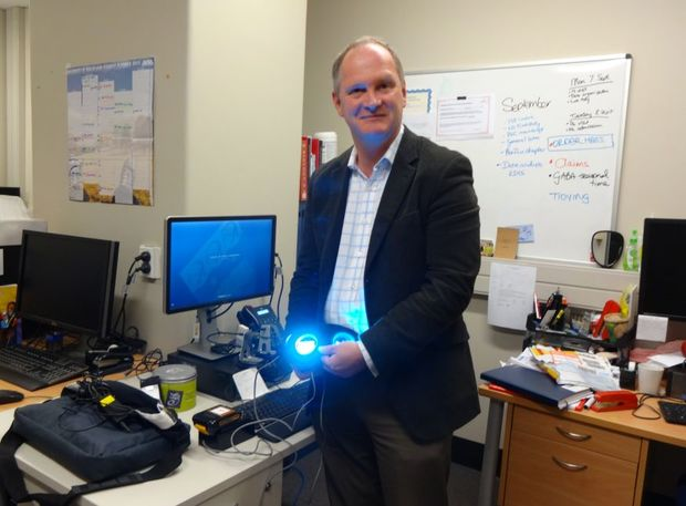 Guy Warman with a pair of light-producing goggles, which the team uses to give light therapy to patients during surgery.
