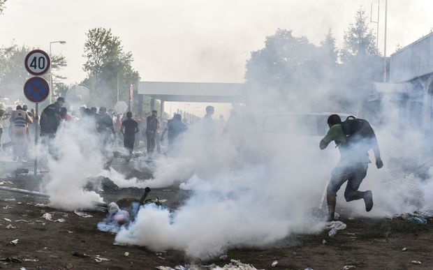 Migrants run away from tear gas thrown by Hungarian anti-riot police officers at the Hungarian border with Serbia near the town of Horgos.
