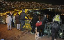 People in the city of Valparaiso keep a close eye on the shoreline after a massive quake hit off the Chilean coast.