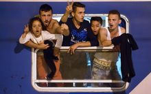 Migrants react as they wait in a train at the railway station, near the Slovenian-Croatian border in Dobova, Brezice, on September 17, 2015.