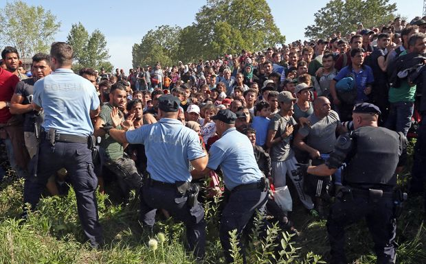 Migrants break a police cordon as they rush to waiting buses in Tovarnik, close to the Croatian-Serbian border on 17 September.