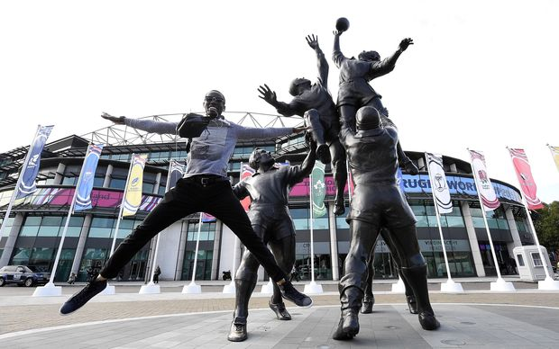 A man jumps next to a statue outside Twickenham Stadium on the eve of the Rugby Union World Cup opening match.