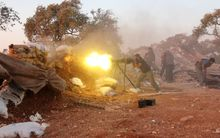 A rebel fighter fires heavy artillery during clashes with government forces and pro-regime shabiha militiamen in the outskirts of Syria's northwestern Idlib province on September 18, 2015.