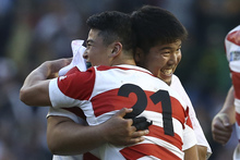 Japan's prop Kensuke Hatakeyama (L) embraces Japan's scrum half Atsushi Hiwasa (R) after winning the Pool B match of the 2015 Rugby World Cup with South Africa.