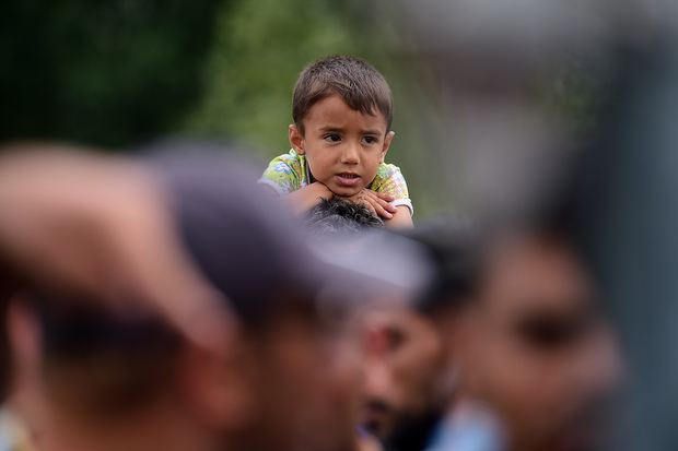 A young migrant boy sits on his father's shoulders at the Hungarian-Austrian border in Heiligenkreuz, Austria.