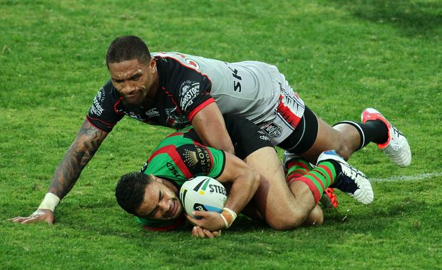 South Sydney Rabbitohs' Dylan Walker being tackled by New Zealand Warriors' wing Manu Vatuvei.