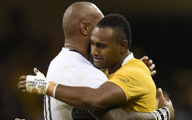 Cousins Tevita Kuridrani (Australia) and Nemani Nadolo (Fiji) embrace following their team's Rugby World Cup clash in Cardiff.