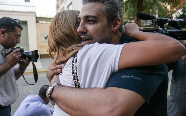 Canadian Al-Jazeera journalist Mohamed Fahmy hugs his wife Marwa after being dropped off by authorities following his release from jail.