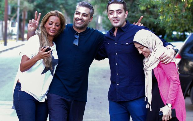 Al-Jazeera journalist Mohamed Fahmy, left, and his colleague Baher Mohamed celebrate with their wives Marwa (l) and Jihan (r) following their release from jail.
