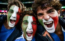 Italy rugby fans cheer on their team.