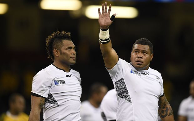 Flying Fijians prop Isei Colati [R] waves goodbye to the Rugby World Cup.