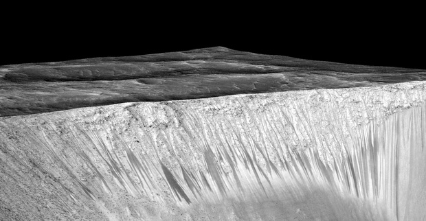 The dark streaks on the walls of Garni crater are hypothesized to be formed by flow of briny liquid water. The image is produced by draping an orthorectified image on a Digital Terrain Model (DTM) of the site.