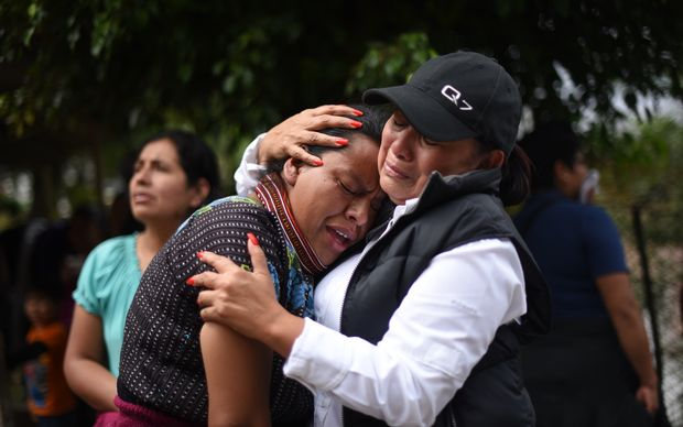 Women cry outside a provisional morgue in the village of El Cambray.