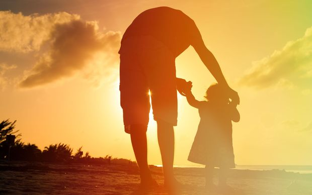 Father and child silhouette on beach generic