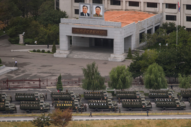 Empty military vehicles ahead of the parade before a building displaying portraits of late North Korean leaders Kim Il-Sung (top L) and Kim Jong-Il (top R) in Pyongyang.