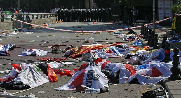 Turkish riot police forces secure the site of twin explosions. Victims' bodies are covered with banners and flags, Ankara, October 10, 2015.
