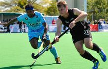 Steve Edwards of the Black Sticks is tackled by Birendra Lakra of India.