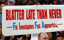 Fan holds a banner protesting against Sepp Blatter prior to Euro 16 qualifying match between England and Estonia at Wembley on October 9, 2015 in London.