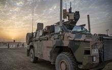 A camouflage painted armoured vehicle sits against a sunset