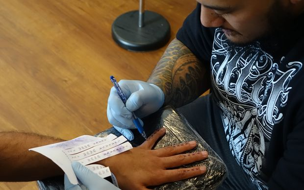Tattoo artist Chris Amosa preparing to tattoo a design by Vaimaila Urale as part of the 'Typeface' live tattoo session for the Avondale Whau Arts Festival.