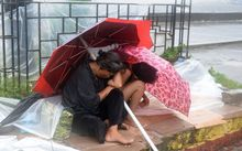 A mother shelters with her son from the wind and rain brought on by typhoon Koppu along Roxas boulevard in Manila.