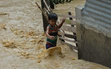 A child wades through floodwaters near his residence at a village in Santa Rosa town, Nueva Ecija province, north of Manila.