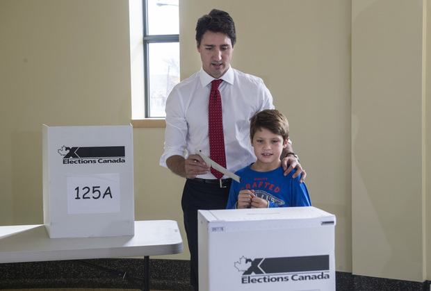 Liberal leader Justin Trudeau carries his vote to the ballot box accompanied by his son Xavier.