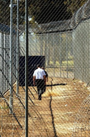 A Sept. 9, 2005 file photo of a guard walking inside the perimeter fence and razor wire that surrounds Villawood Detention Centre in Sydney.