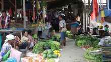 Papuan women sell produce in an old market in Sentani