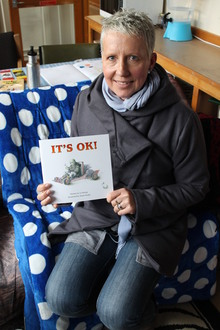 "Photo of Jo Heslop with the book she has written, ""It's OK""."