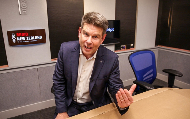 John Campbell sitting at a temporary cardboard desk in the Checkpoint studio at Radio New Zealand.
