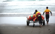 Surf Life Saving lifeguards test out a rescue boat at Muriwai Beach, Auckland.