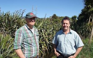 Farmers David Peacocke and Craig Rowlandson stand next to plantings along a stream on David's farm.