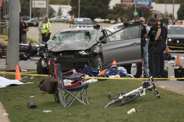 Emergency officials stand over the car that was involved after a suspected drunk driver crashed into a crowd of spectators during the Oklahoma State University homecoming parade.