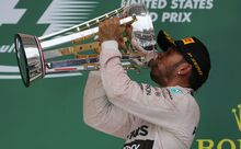 Lewis Hamilton celebrates on the winners podium.