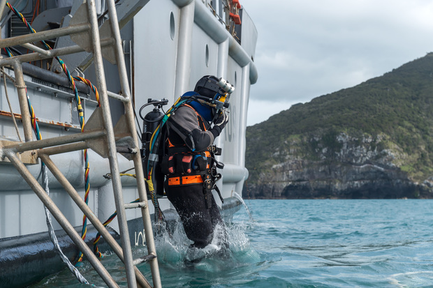 Navy diver Luke Gordon enters the water in Akaroa Harbour from HMNZS Manawanui during training ahead of a search and recovery operation at the site of sunken fishing vessel Jubilee on 26 October 2015.