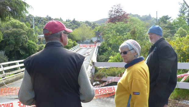 Residents on Bridge Road in Birchville standing near their collapsed bridge over the Akatarawa River.