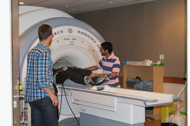 Christchurch collaborators are helping to run the scans. Mustafa Almuqbel prepares a research team member for his MRI. Tracy Melzer of the New Zealand Brain Institute is in the foreground.