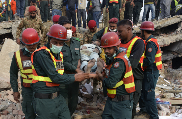 Pakistani rescuers move a man rescued from under the rubble of the collapsed factory.