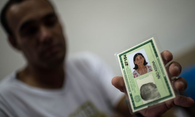 "Marcello Jose Felicio, 30, shows the ID of his mother Maria ""Gracita"" who disapeared during the mudslide that buried their village, Bento Rodrigues, in Mariana, Brazil, on 8 november, 2015 AFP PHOTO / CHRISTOPHE SIMON"
